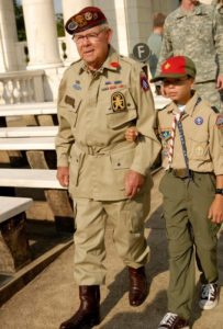 A Boy Scout helps escort a veteran from his bus into Arlington National Cemetery's Memorial Amphitheater for the Operation Dragoon commemoration ceremony, Aug. 5 2009. Source: Wikimedia Commons